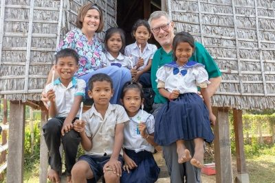 Dr. Scott Bernardy posing with happy children in front of hut with toothbrushes