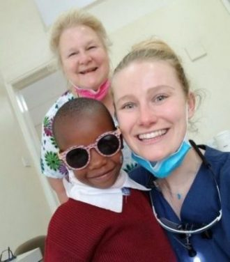 Women dental hygienists with cool kid in sunglasses