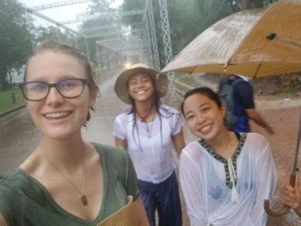 Women in pouring rain take selfie and having fun.