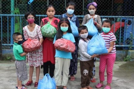 Nepal children holding bags of food for their families