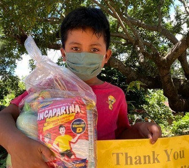 child overseas holding bag of food and thank you sign