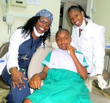 two dentists treating young girl's smile